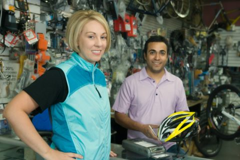 Bike shop staff answering a new bicyclist's questions.