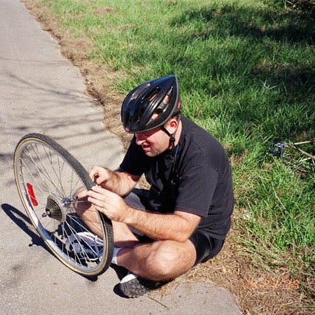 Jim changing a flat tire along the side of the road.