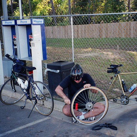 Jim changing a flat tire on his bike at a gas station.