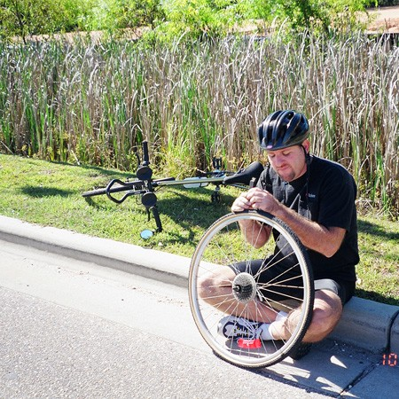 Jim gets yet another flat tire along the road on a day of biking.