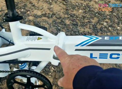 Pointing to the place on the bike frame where this eBike folds in half.