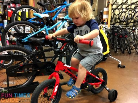 My son trying out a 12-inch bike with training wheels in the bike shop.